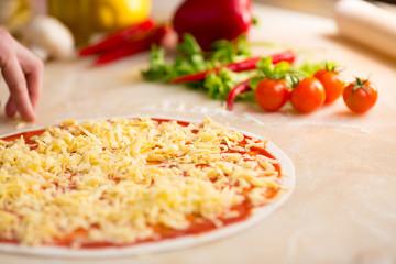 Italian pizza preparation. Cheese covering.