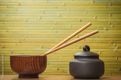 Chopsticks and bowls on bamboo background