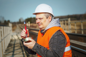 Railroad worker  with canned meat on a railway