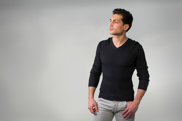 Handsome latin young man standing on grey background.