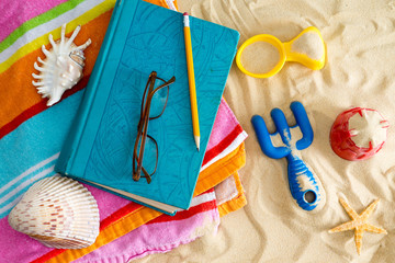 Book and reading glasses on a beach towel