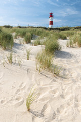 Sand dune and lighthouse on background.