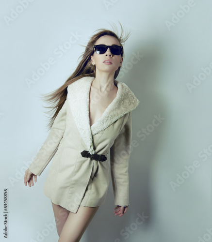 Girl wearing sunglasses and a white fur coat