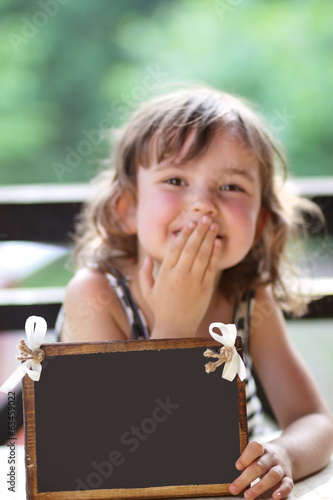 Joyful little girl holding a sign for your sample text