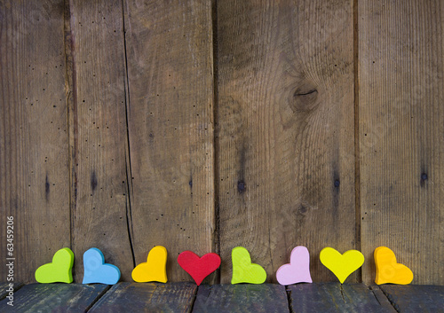 Colorful hearts on a wooden background for a greeting card.