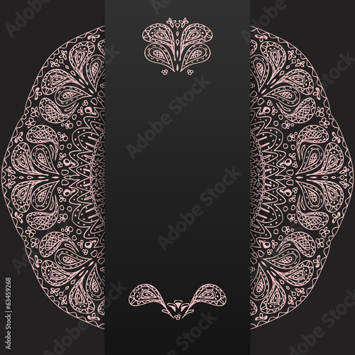 Abstract dark background with light lacy mandala pattern.