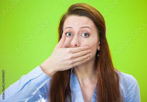 Woman covering mouth with on eland, speak no evil