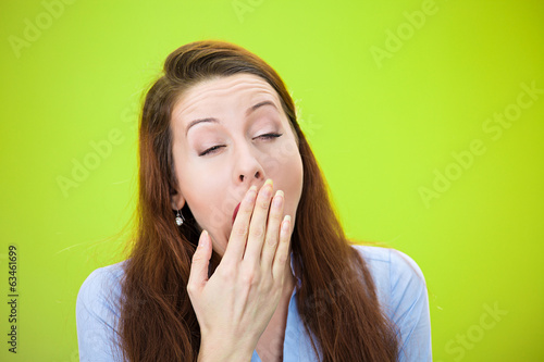 Sleepy yawning woman isolated on green background
