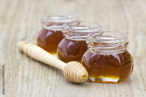 three jars of honey and honey dipper on wooden background