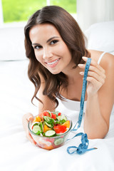 Woman with salad and measure tape, indoor