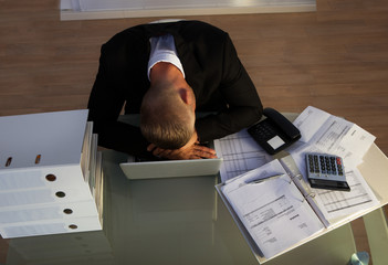 Exhausted businessman sleeping an a stack of files