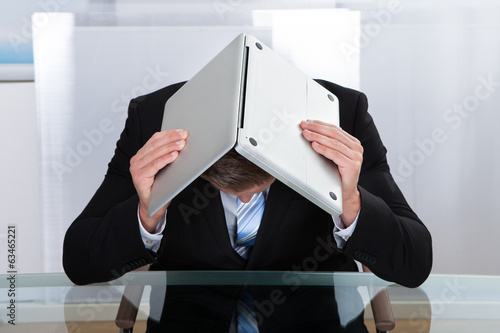 Depressed businessman hiding under his laptop