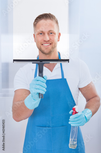 Male janitor using a squeegee to clean a window