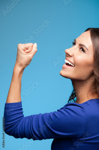 Happy gesturing young woman, over blue