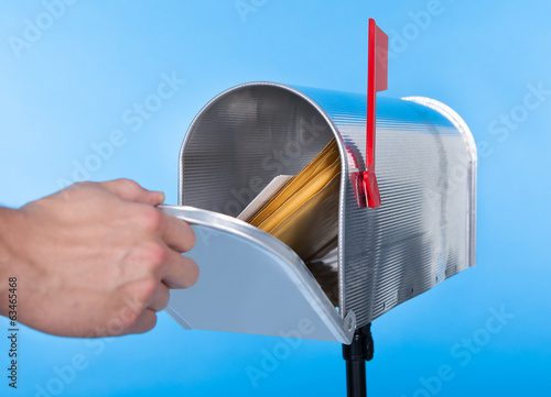 canvas print picture Man opening his mailbox to remove mail