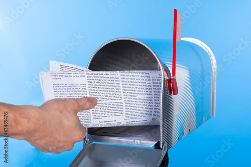 Man removing a newspaper from his mailbox