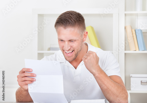 Man cheering in jubilation as he reads a letter