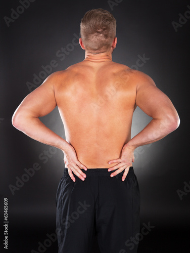 canvas print picture Strong muscular man with backache