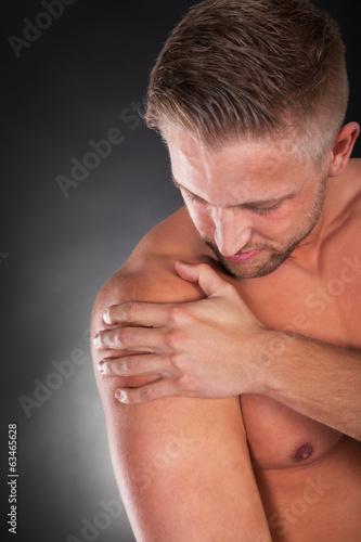 Muscular sportsman massaging his shoulder