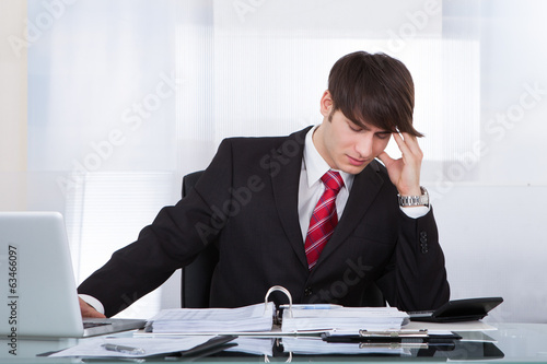 Businessman Suffering From Headache While Calculating Finance