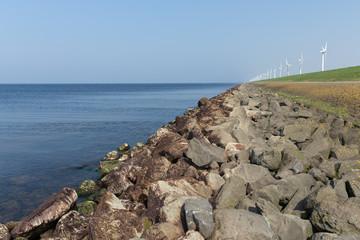 Dutch dike along the sea with wind turbines