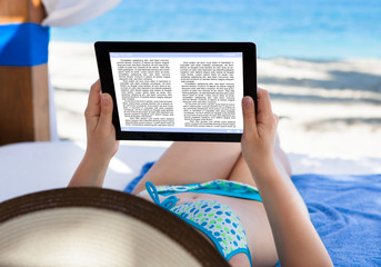 Woman Reading E-Book At Beach