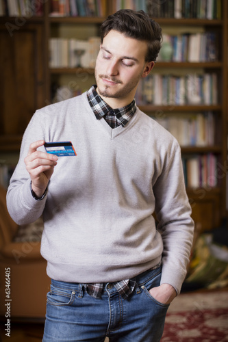 Attractive young man holding credit card, looking at it