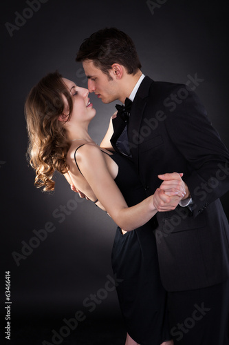 Elegant Couple Dancing Over Black Background