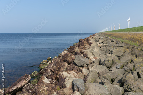 Dutch dike along the sea with wind turbines