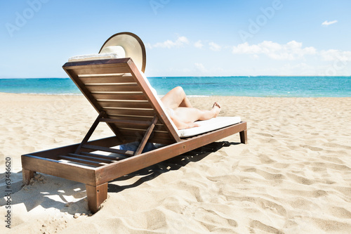 Woman Sunbathing On Deck Chair At Beach