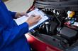 Leinwanddruck Bild - Mechanic Holding Clipboard In Front Of Open Car Engine