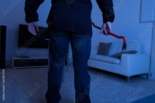 Thief Holding Crowbar In Living Room