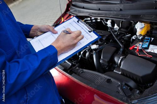 Leinwanddruck Bild Mechanic Holding Clipboard In Front Of Open Car Engine