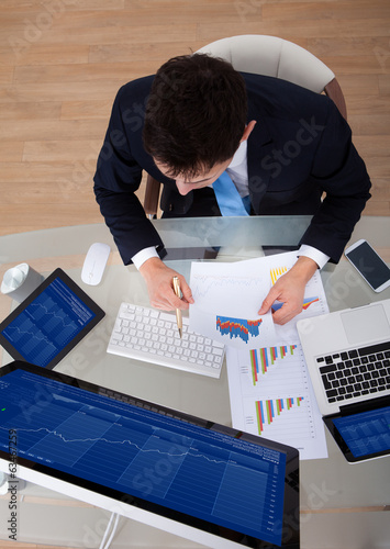 Businessman Examining Graphs At Desk
