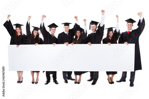 Cheerful excited graduate students showing empty banner