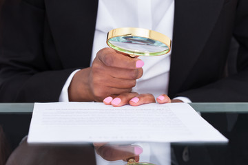 Businesswoman Using Magnifying Glass To Read Document At Desk