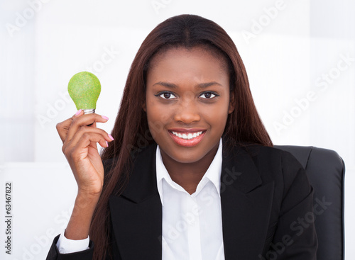 Businesswoman Holding Green Electric Bulb In Office