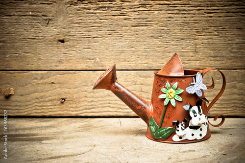 old and rusty watering can with wood background