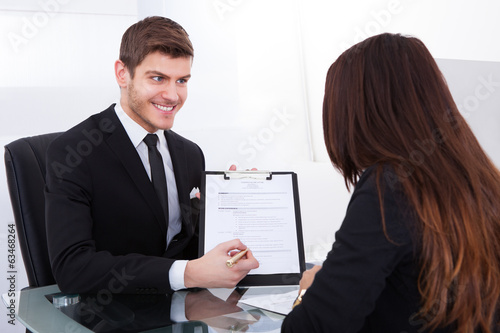 Businessman Showing Document To Female Colleague