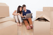 Couple Using Laptop Together In New Home