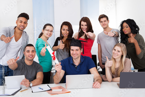 Student Holding Degree With Classmates Gesturing Thumbs Up