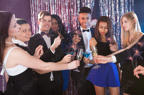Happy Friends Toasting Drinks At Nightclub