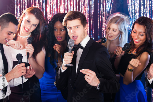 Man Singing Into Microphone With Friends At Karaoke Party