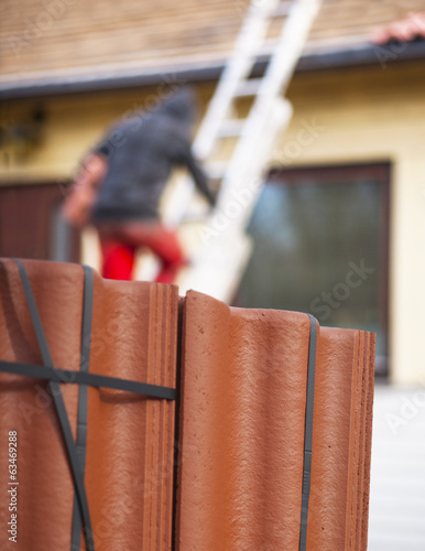 worker putting new roof tiles on house