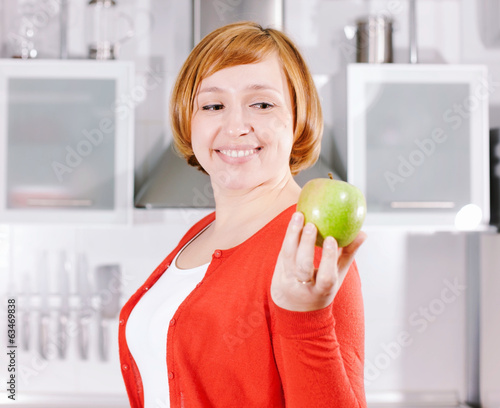 Redhead housewife with apple at kitchen