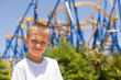 Boy next to a roller coaster