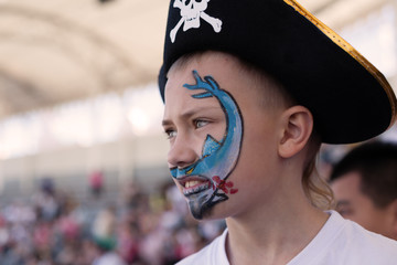 Boy painting face in pirate hat