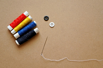 Sewing accessories: thimble, thread on a wooden table
