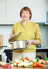 Smiling mature woman cooking  vegetarian lunch with potatoes
