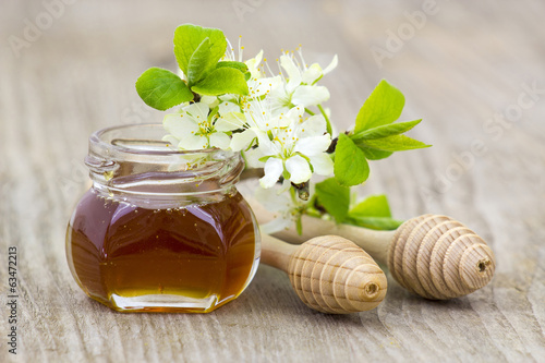 Honey in a jar, flowers and honey dippers on wooden background